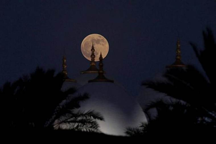 A lunar eclipse of a full Blood Moon rises behind the Sheikh Zayed Grand Mosque in Abu Dhabi, United Arab Emirates (Source REUTERS)