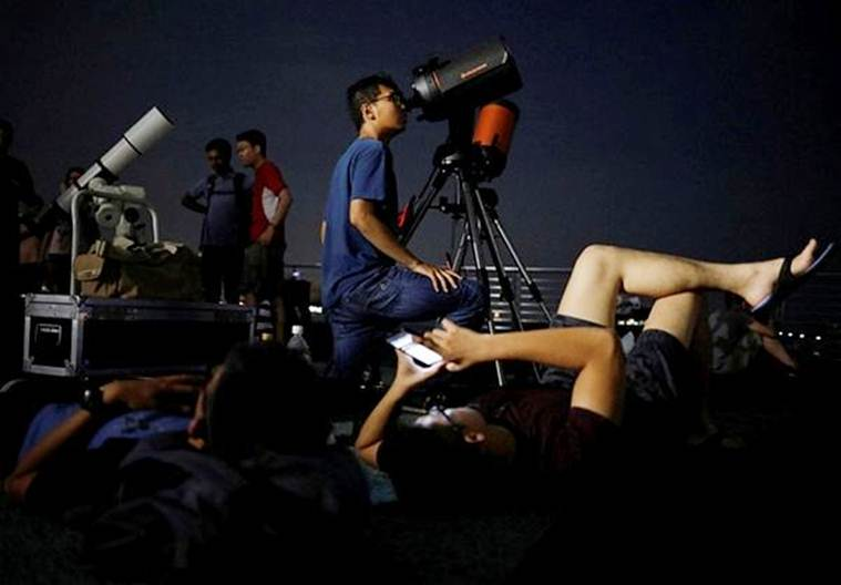 Astronomy enthusiasts prepare their telescopes to see the lunar eclipse at Marina South Pier in Singapore (Source, Reuters)